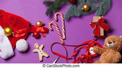 Christmas gifts and candy on violet background