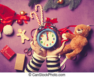 Female hands are holding an alarm clock on christmas gifts...