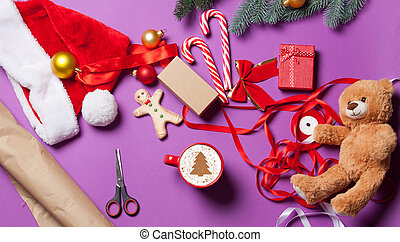 Christmas gifts and cup of coffee on violet background