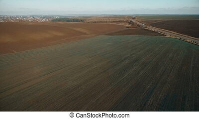Aerial view of fields and roads on which freight car rides...