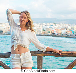Pretty woman posing against cityscape with bay. Place for...