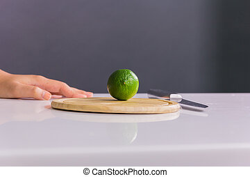 Fresh and sour green lime or lemon, half cut with knife on...