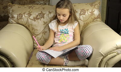 Sweet girl draws sitting on a chair
