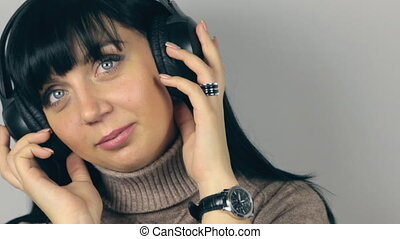 Beautiful brunette strongly surprised listening to music on headphones
