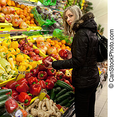 Pretty young woman shopping for fruits and vegetables at a...