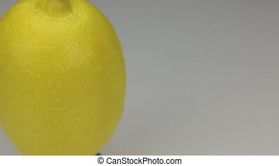 Extreme closeup yellow lemon in drops of dew rotates on its...
