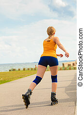 Young woman rollerblading outdoor on sunny day - Holidays,...