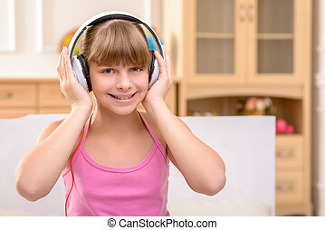 Cheerful little girl listening to music - Devoted music fun....