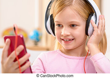 Vivacious little girl listening to music - Best way to...