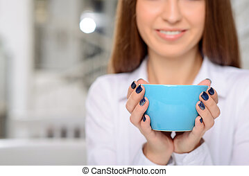 Pretty young woman drinking coffee - Warm your heart. Close...