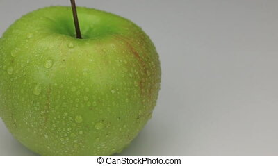 Extreme closeup green apple in drops of dew rotates on its...
