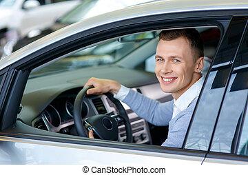 Pleasant man choosing car in auto show - Feeling happy...