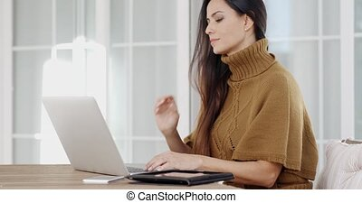 Attractive woman sitting typing on a laptop