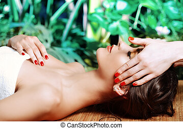 head massage - Manual therapy. Beautiful young woman getting...