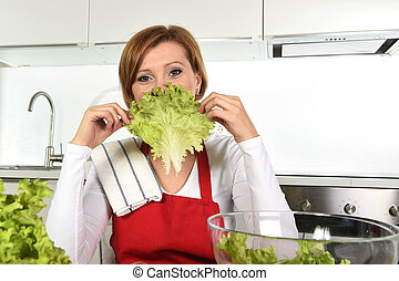 young beautiful woman in red apron at home kitchen preparing...