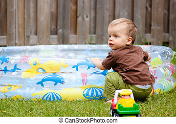 Child playing by the kiddie pool - A caucasian child sits by...
