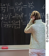 pretty college student standing in front of a chalkboard in a classroom and trying to find a solution to a math problem