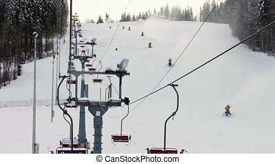 Snow machine gun on a ski slope. - Yellow snow cannons stand...