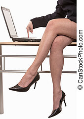 Businesswoman sitting on table typing on laptop