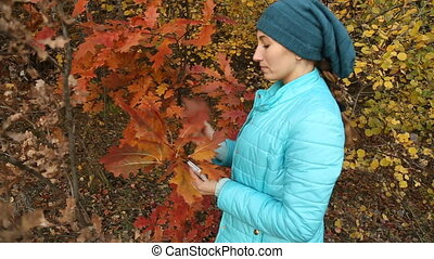 girl tearing leaves - girl tearing the leaves in the autumn...