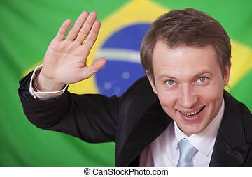 greetings from brazil - happy businessman waving in front of...