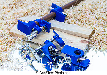 dark blue pipe clamp on sawdust background