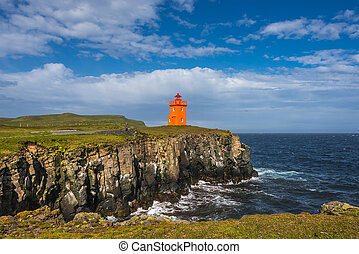 Orange lighthouse at seashore of Grimsey island nearby...