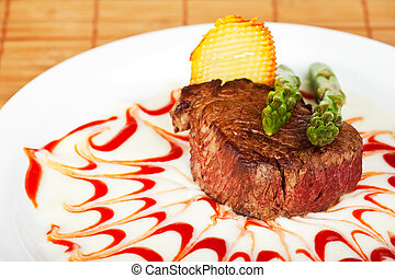 closeup of a beef steak with green asparagus on a white background