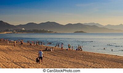 vietnamese people walk on beach swim in sea at dawn -...