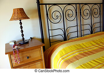 Hotel Room - Detail of bed and bedside table with lamp in a...