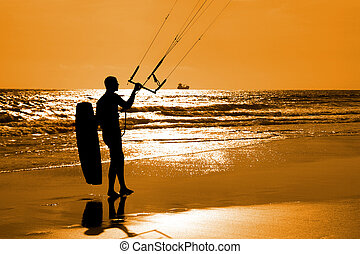 Kitesurfer silhouette moving on the sand an holding...