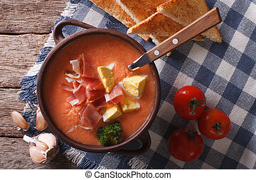 Salmorejo soup with ham and eggs in a bowl close-up....