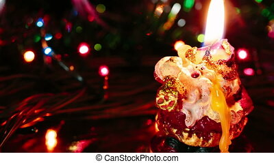 Burning candle in the shape of santa claus.