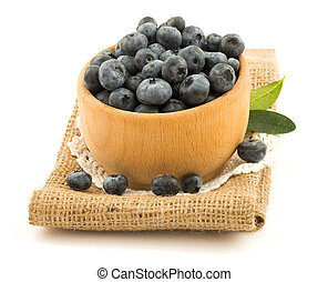 Blueberries in the wooden bowl with green leaves on the...