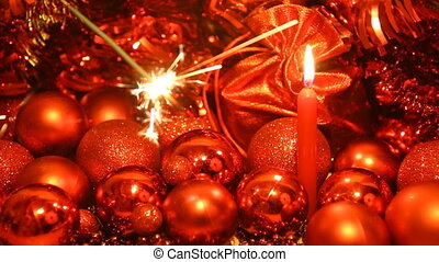 Christmas sparkler with candle - Sparkler and candle on red...