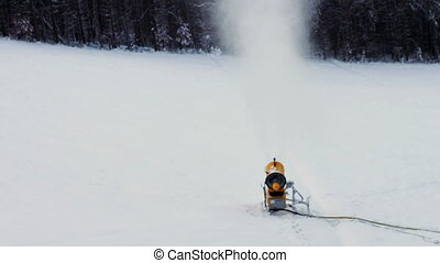 Snow machine gun on a ski slope - Yellow snow cannons stand...