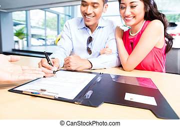 Asian Couple signing sales contract for car at dealership