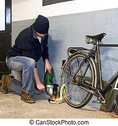 Bike thief - Bicycle thief busy breaking the lock with a...