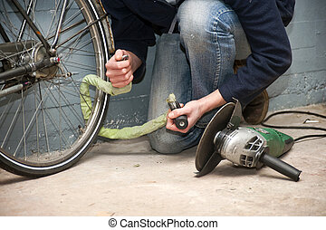 Bike theft - Thief opening the lock of a bicycle with a...