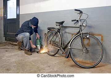 Bicycle thief busy breaking the lock with a portable...