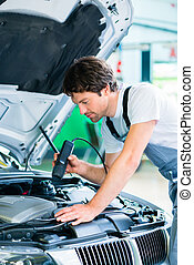 Mechanic with diagnostic tool in car workshop
