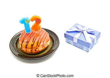 donut with twelve years birthday candle and gift on white