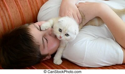 Teenage boy playing with a kitten on couch - Teenage boy...