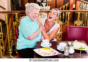 Granny and granddaughter laughing in cafe - Senior woman and...
