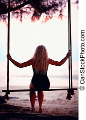 young woman sitting on tree wings at the beach