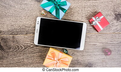 christmas gifts on wood - Tablet computer with blank black...
