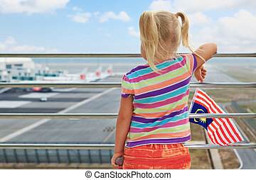 Young passenger looks at planes in airport - Little baby...