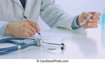 Doctor hand writing a medical recipe paper