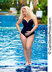 beautiful plus size woman posing in the pool