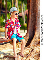 cute fashionable boy on swings at the beach